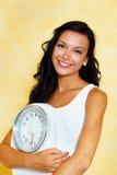 Femme avec des échelles après un régime réussi Image stock