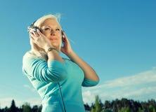Femme avec des écouteurs Photographie stock libre de droits