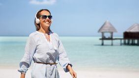 Femme avec des écouteurs marchant le long de la plage d'été photo stock