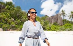 Femme avec des écouteurs marchant le long de la plage d'été images libres de droits