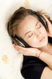 Femme avec des écouteurs se couchant sur le sofa dans le salon Photo libre de droits