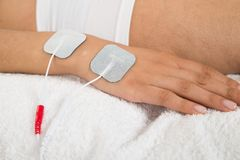 Femme avec des électrodes sur sa main Photographie stock