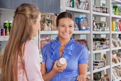 Femme avec des achats d'ami dans le supermarché Photos libres de droits