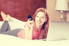 Femme avec des achats d'ordinateur portable sur la ligne montrant la carte de crédit images libres de droits