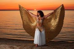 Femme avec des ailes au coucher du soleil Photo stock