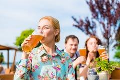 Femme avec des amis dans le jardin de bière Photo stock
