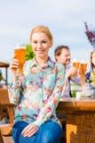 Femme avec des amis dans le jardin de bière Photos libres de droits