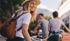 Femme avec des amis en tournée de ville avec le vélo Images stock