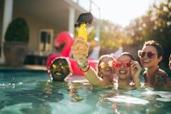Femme avec des amis faisant le selfie à la réception au bord de la piscine Photographie stock