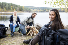 Femme avec des amis préparant le feu sur au bord du lac Photos stock