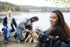 Femme avec des amis préparant le feu sur le camping de Lakeside Photographie stock libre de droits