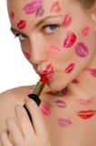Femme avec des baisers sur le visage dans le rouge à lèvres et des lèvres Images stock