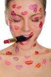 Femme avec des baisers sur le visage et le rouge à lèvres dans la bouche Photo libre de droits