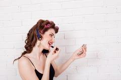 Femme avec des bigoudis parlant sur le maquillage de téléphone photo libre de droits