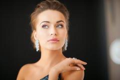 Femme avec des boucles d'oreille de diamant Images stock