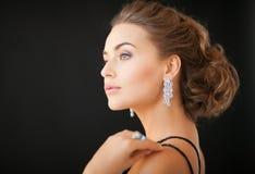 Femme avec des boucles d'oreille de diamant Image stock