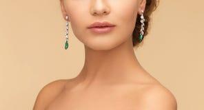 Femme avec des boucles d'oreille de diamant et d'émeraude Photo stock