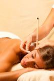 Femme avec des bougies d'oreille et le massage de gemme Photographie stock libre de droits