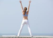 Femme avec des bras augmentés à la plage Image stock