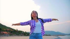 Femme avec des bras augment?s sur un portrait en gros plan de plage tropicale de belle brune mignonne europ?enne, jeune femme ou clips vidéos