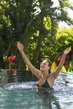 Femme avec des bras augmentés dans la piscine extérieure Images libres de droits