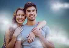 Femme avec des bras autour de l'homme sur le fond de vert bleu avec des nuages Photos stock