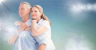 Femme avec des bras autour de l'homme sur le fond de vert bleu avec les nuages et la fusée Image stock