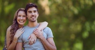 Femme avec des bras autour de l'homme sur le fond vert trouble Images stock