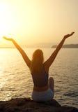 Femme avec des bras grands ouverts au coucher du soleil Images stock