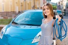 Femme avec des câbles devant la voiture Images libres de droits