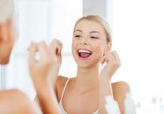 Femme avec des dents de nettoyage de fil dentaire à la salle de bains Image stock