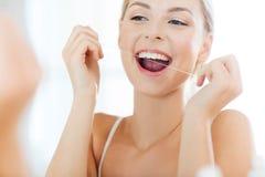 Femme avec des dents de nettoyage de fil dentaire à la salle de bains Photos libres de droits