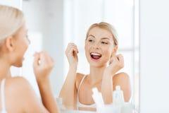 Femme avec des dents de nettoyage de fil dentaire à la salle de bains Photographie stock