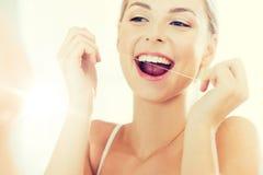 Femme avec des dents de nettoyage de fil dentaire à la salle de bains Images libres de droits