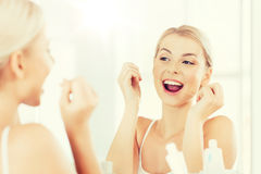 Femme avec des dents de nettoyage de fil dentaire à la salle de bains Image libre de droits