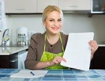 Femme avec des documents à la cuisine photo libre de droits