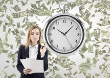 Femme avec des documents dans une chambre avec un chronomètre et des dollars Photographie stock libre de droits