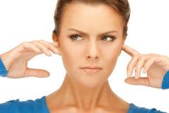 Femme avec des doigts dans des oreilles Photographie stock