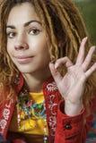 Femme avec des dreadlocks rendant le signe tout correct photos stock