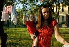 Femme avec des enfants dans la blanchisserie accrochante de jardin dehors photo stock