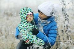 Femme avec des enfants dans le domaine d'hiver Photos libres de droits