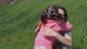 Femme avec des enfants en nature Maman et filles sur la pelouse verte Enfants dans le rose Famille en stationnement banque de vidéos