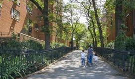 Femme avec des enfants marchant par la rue dans le secteur de Blookyn, à New York City Photographie stock libre de droits