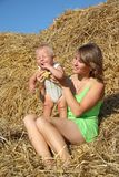 Femme avec des enfants se reposant sur une meule de foin Images stock