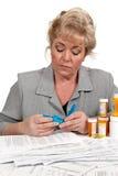 Femme avec des factures de soins de santé et coupeur de pillule Photographie stock
