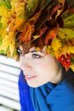 Femme avec des feuilles d'érable sur la tête Image stock
