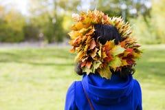 Femme avec des feuilles d'érable sur la tête Photographie stock libre de droits