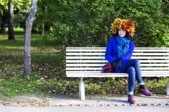 Femme avec des feuilles sur la tête sur le banc Photographie stock