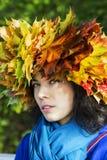 Femme avec des feuilles sur le regard principal soupçonneusement Photographie stock