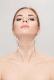 Femme avec des flèches sur le visage au-dessus du fond gris escroquerie de levage de cou photo libre de droits
